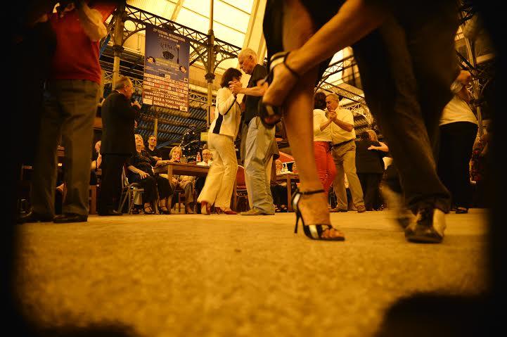 Parejas bailando tango en Joventango. la toma, desde el piso, muestra en primer plano los pies de una bailarina. de fondo, varias parejas bailando