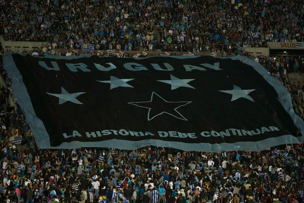 bandera de Uruguay desplegada por hinchas en el estadio centenario tradiciones uruguayas