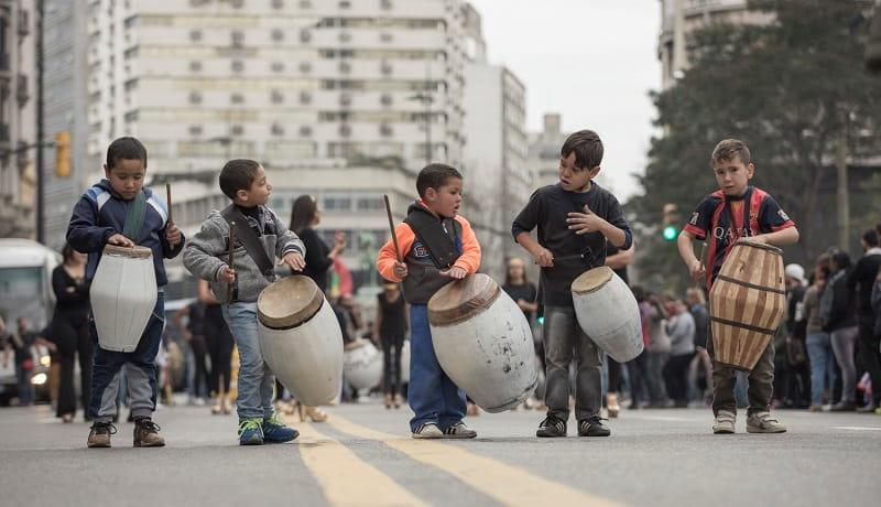Varios niños tocan candombe con sus tambores por la avenida 18 de julio