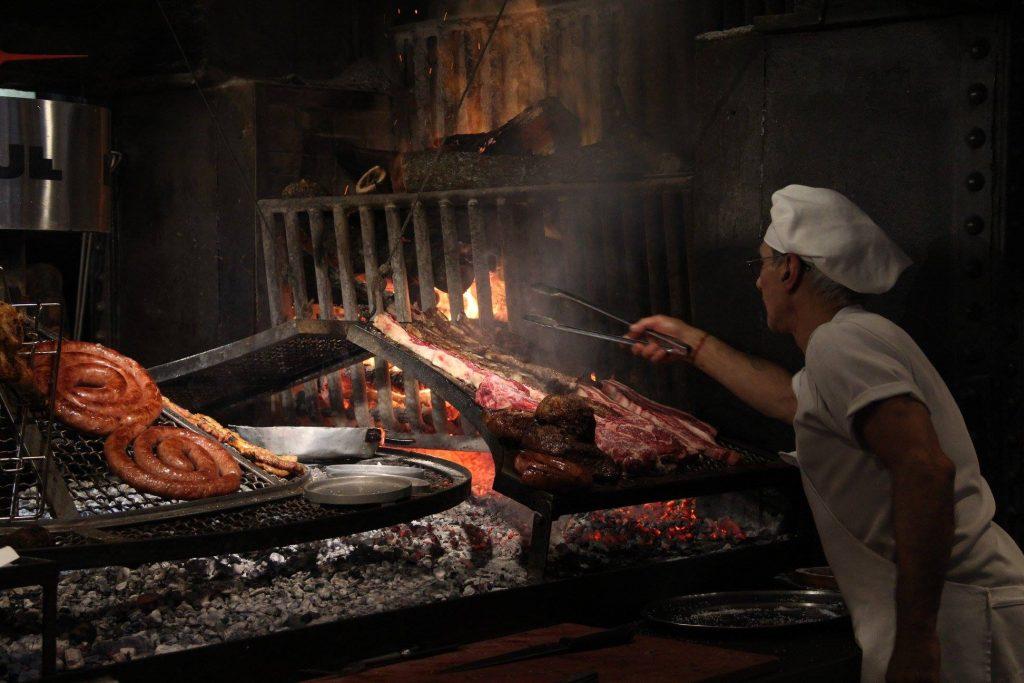 asador moviendo la carne sobre una parrilla tradiciones uruguayas