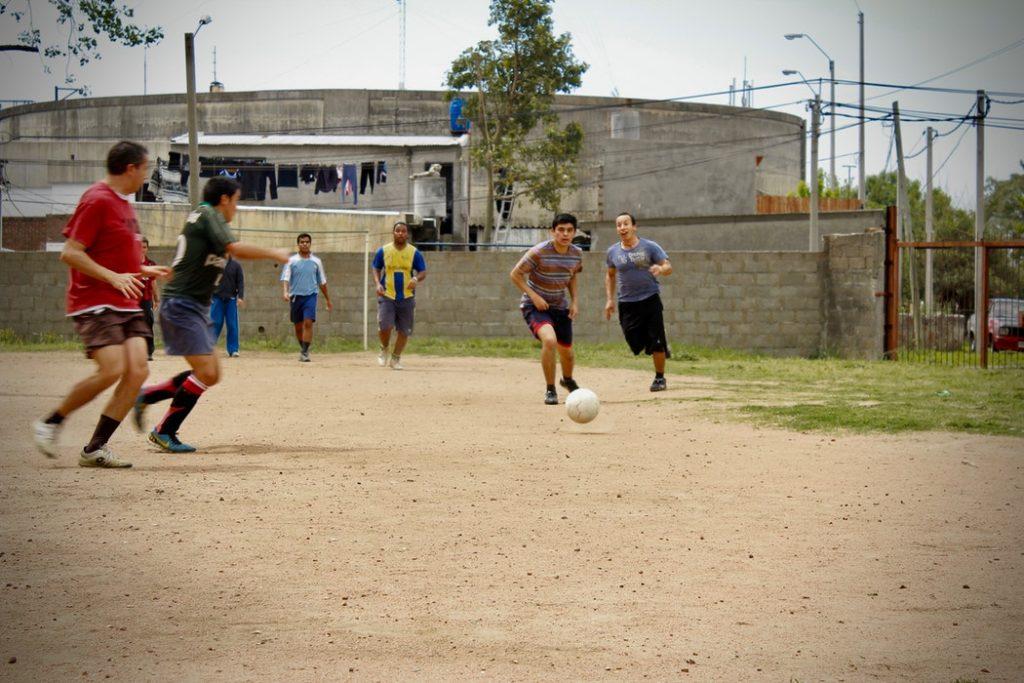jóvenes jugando al fútbol en una cancha de barrio sin césped tradiciones uruguayas