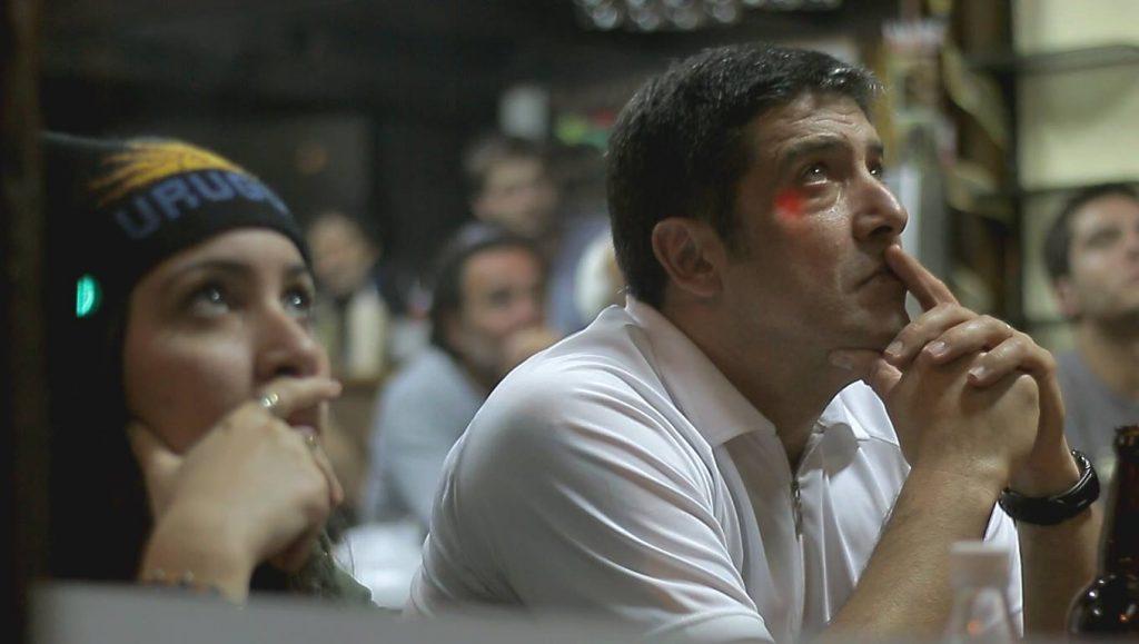 hinchas mirando serios un partido de Uruguay en la TV de un bar fútbol uruguayo