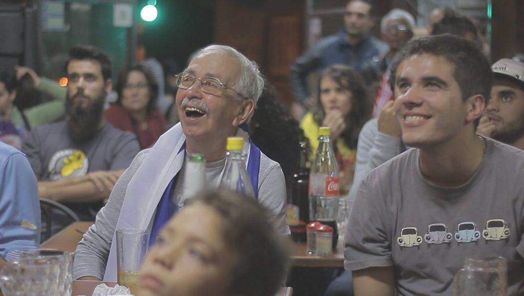 hinchas mirando sonrientes un partido de uruguay en un bar fútbol uruguayo