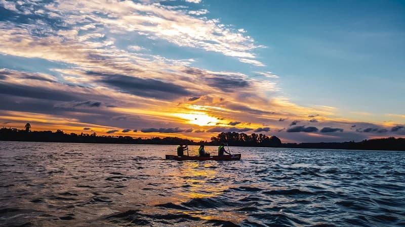 Imagen de tres personas navegando al atardecer sobre una canoa en el río