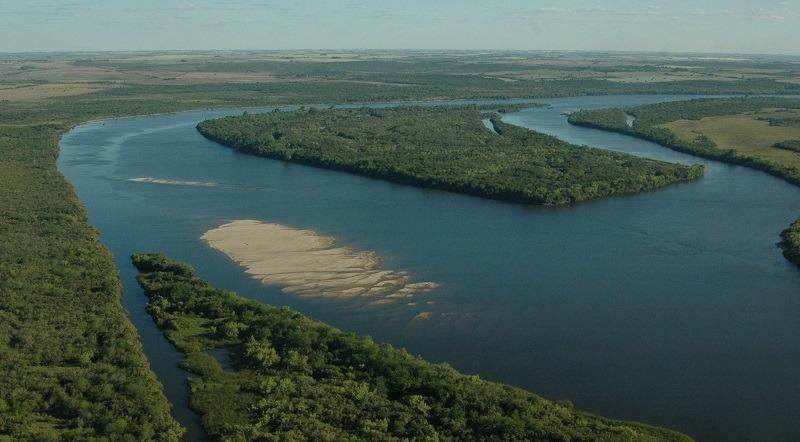 Imagen aérea de un recodo del Río Negro con una isla sobre la que hay mucha vegetación