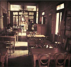 Imagen de un salón antiguo con piso de madera, en el que se observan varias mesas y sillas de estilo antiguo, de madera