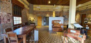 Imagen interior de una viaja casona; las paredes tienen ladrillo a la vista; en el salón hay varias mesas, sillas y otros mobiliarios antiguos de madera