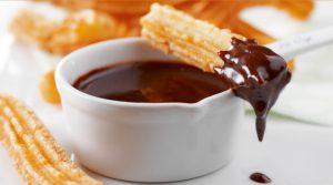 Un churro con chocolate en la punta, sobre una pequeña taza de chocolate.