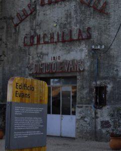 """Imagen de un un cartel de madera con la inscripción """"Casa Evans"""" y una breve descripción del eduificio, debajo. Al fondo, fuera de foco, se observa un viejo edificio con un cartel en letras rojas de metal que dice """"casa Evans"""""""