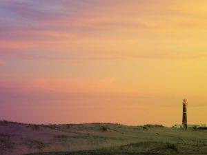 Imagen de un atardecer, en un paisaje de dunas con algo de vegetación; en el cielo aparecen diversos tonos de amarillo, rosados, violetas y naranjas; en el fondo se observa un faro