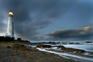 Imagen de un faro con su luz encendida en una noche nublada y oscura; a su frente se observan las rocas y parte del Océano Atlántico golpeando contra ellas
