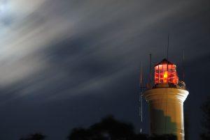 Imagen de la cima de un faro, en una noche nublada. La luz del faro es roja