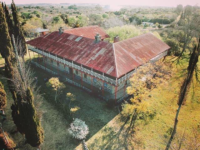 Vista aérea del Hotel Conchillas: un viejo edificio en forma de herradura rectangular, con techos a dos aguas rojo, en medio de un paisaje arbolado