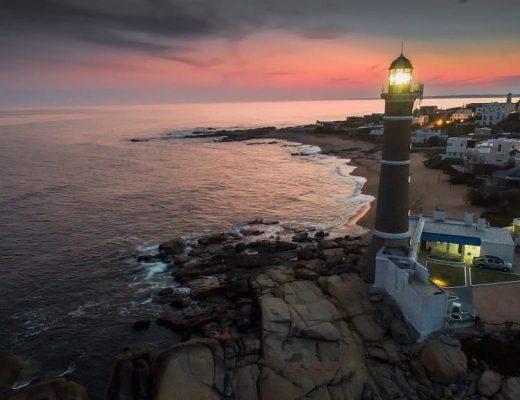 Imagen al atardecer del faro iluminado de José Igacio; se observa algunas casas a un lado del faro y al otro, el océano.