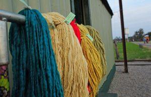 Imagen del costado del edificio de una estación de ferrocarril; en una pared están colgadas lanas teñidas de diversos colores