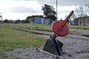 En primer plano, un intercambiador de vías rojo y verde; al fondo, la vida estación de trenes de Mal Abrigo