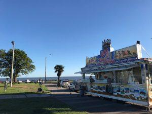"""Imagen del carro de tortas fritas de """"Pepe, el Rey de las Tortas Fritas"""". En el frente tiene imágenes de atractivos turísticos del Uruguay, y sobre el techo, una marquesina con una corona de luces de colores. Detrás del carro, el Río de la Plata."""