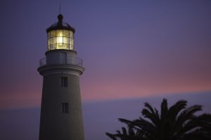 Imagen de la parte superior de un faro; se observa su luz encendida; al fondo el cielo de tonos violetas, naranjas y rosados; a un costado, la copa de una palmera