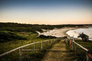 Imagen del ingreso a la playa La Moza; se observa un camino sobre césped delimitado por barandas de madera; al fondo aperece la playa, parte del parque arbolado y el océano