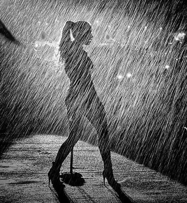 Imagen en blanco y negro desde atrás de una mujer frente a un micrófono de pié, bajo una lluvia intensa