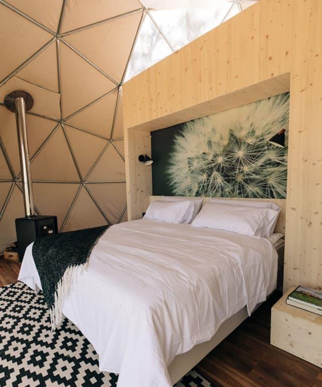 Imagen del interior del domo; se observa un sommier de dos plazas, una pequeña estufa y una alfombra con rombos blancos y negros; arriba, una abertura por donde entra el sol