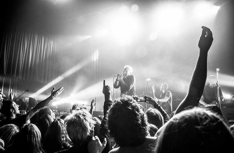 Imagen en Blanco y Negro de Gabriel Peluffo cantando sobre un escenario, con un público numeroso frente a él
