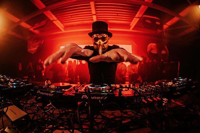 Imagen de un hombre con galera y una máscara dorada con nariz puntiaguda, con las manos extendidas sobre una bandeja de discos