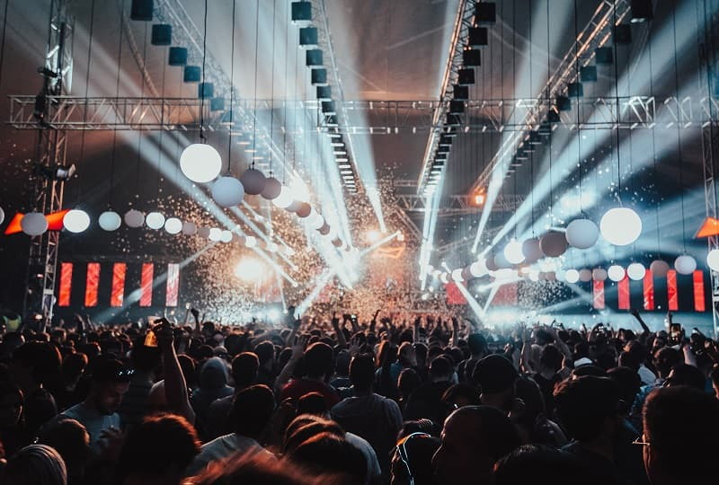 Imagen de la fiesta Coccon; cientos de personas bailando frente a un escenario desde el que salen luces y humo