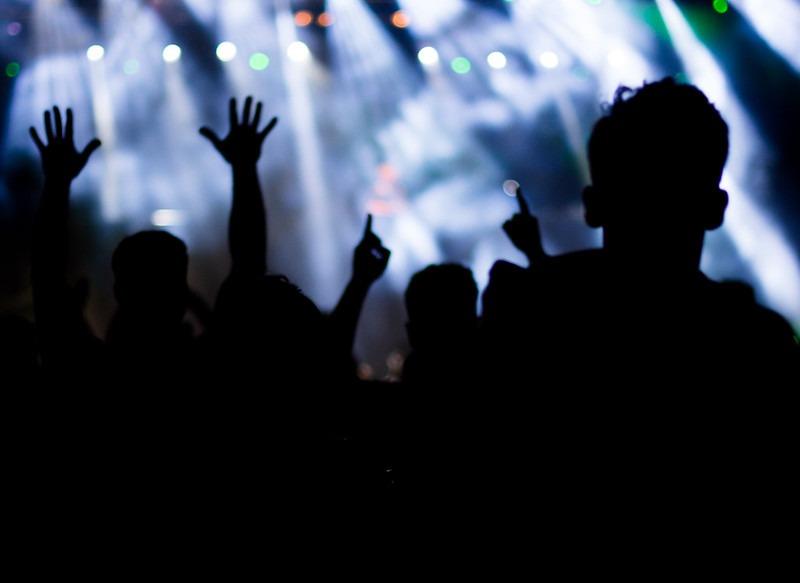 Imagen de una multitud de personas bailando en una fiesta electrónica. Se observan siluetas de personas alzando sus brazos; en el fondo, luces y humo.