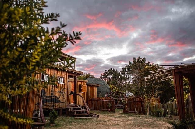 Imagen de varias construcciones de madera, una de ellas en forma de domo,, en medio de la naturaleza. Al fondo se observa el cielo nublado en tonos rosados, naranjas y azules.