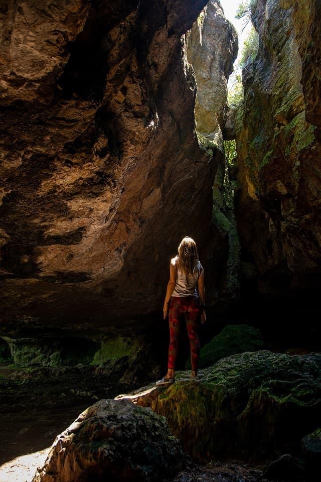 Manuela Da Silveira, parada sobre una gran roca, mirando hacia el espacio abierto por donde entra luz, dentro de una gruta