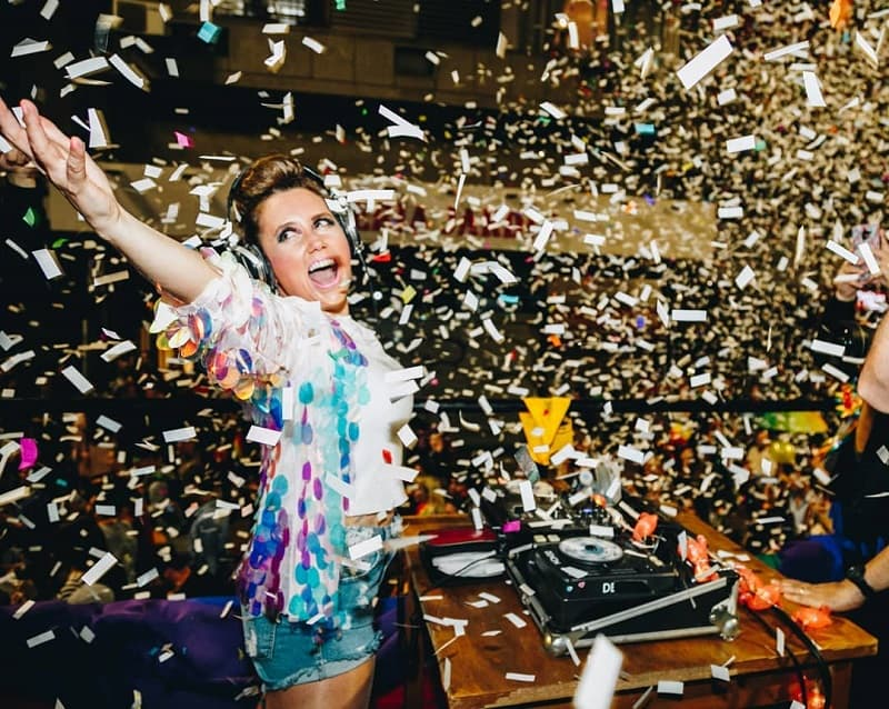 Imagen de Paola Dalto detrás de una bandeja de discos bajo una lluvia de papelitos de dolores