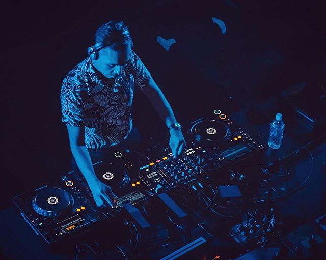 Imagen de un hombre frente a una bandeja tocando música electrónica