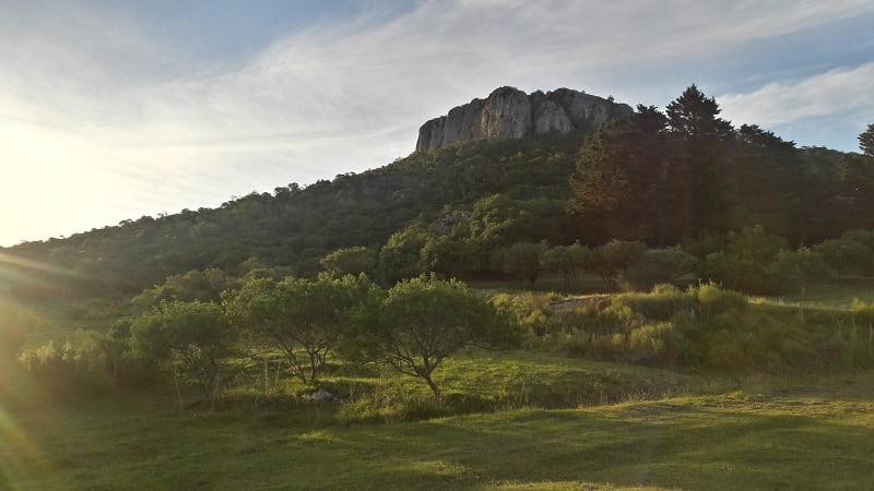 Imagen de un cerro con sus paredes de piedra gris, sobre un paisaje verde, al atardecer