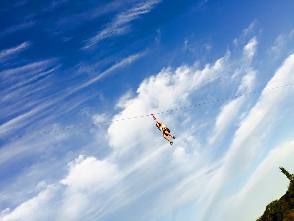 Una mujer lanzándose en tirolesa; al fondo solo se ve un cielo apenas nublado