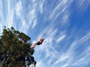Una mujer se lanza en tirolesa; al fondo aparece la copa de un árbol
