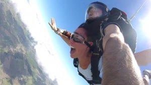 Una mujer salta en paracaídas en tándem, a su espalda un instructor con casco