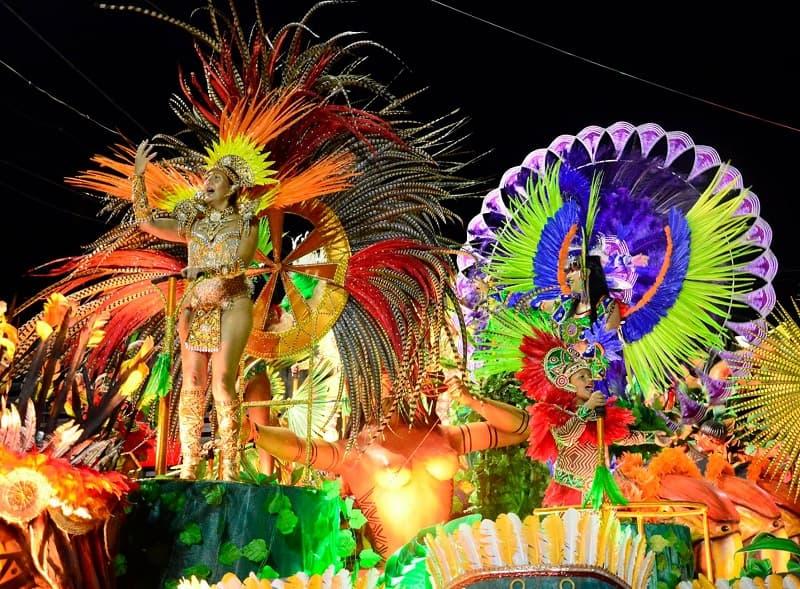 Sobre una corroza llena de colores, varias personas con diferentes disfraces bailan y cantan