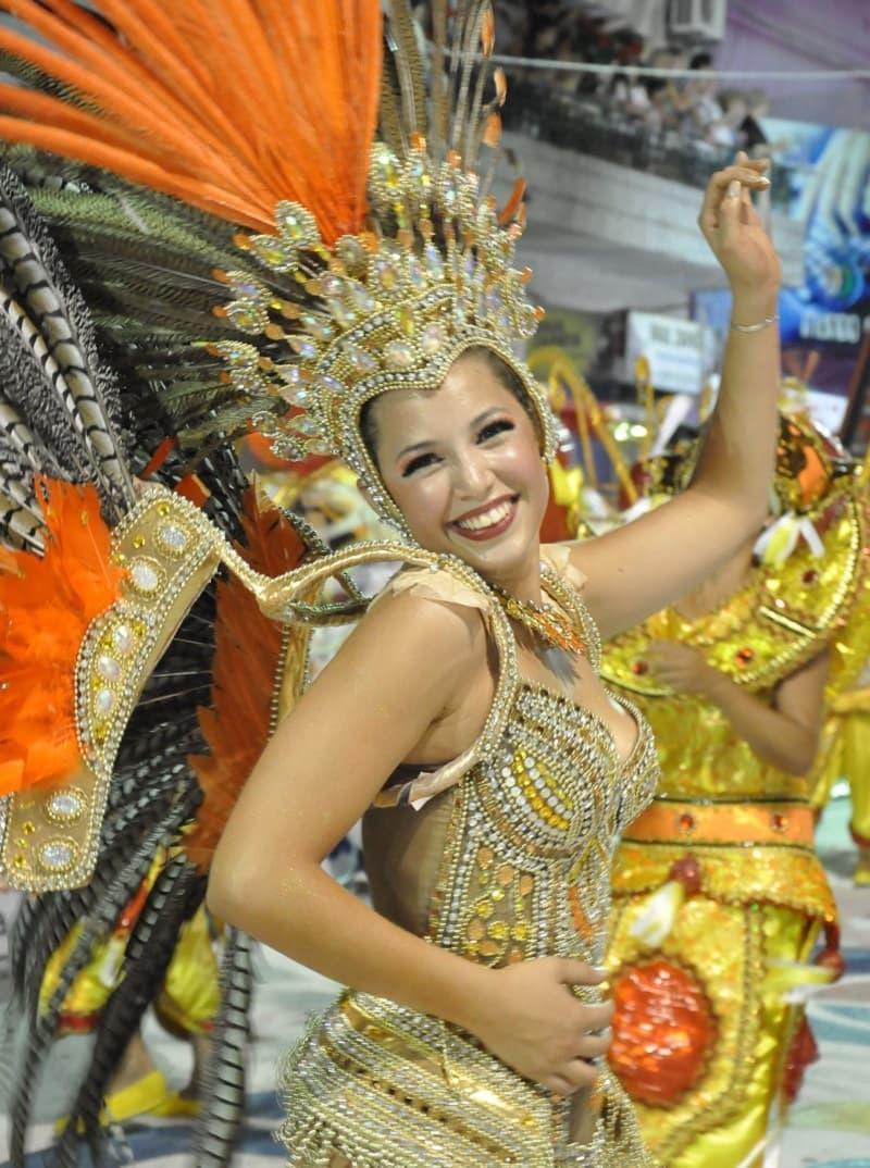 Una vedette, con un diosfraz con plumas naranjas baila y sonríe