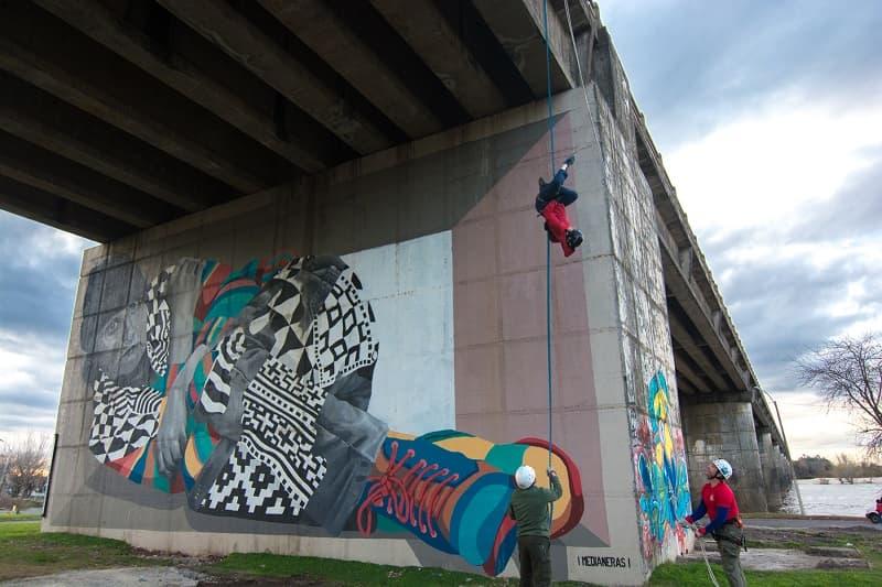 Una persona se lanza por una cuerda colgada a un puente; denajo hay otras dos personas mirando hacia arriba