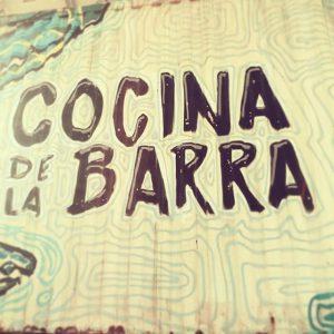 """Imagen de un cartel amarillo y verde que dice, en letras negras, """"Cocina de la Barra"""""""