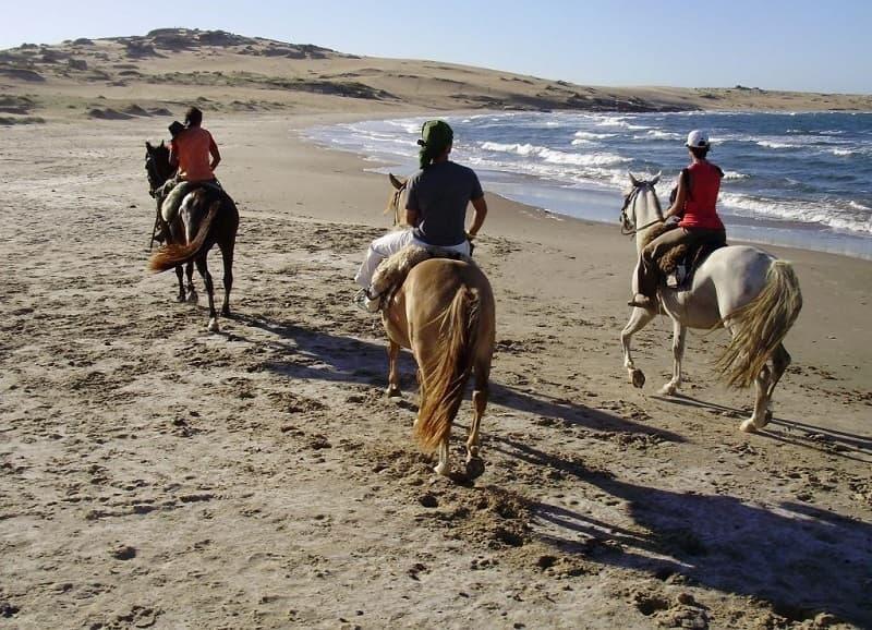 Imagen de tres personas cabalgando sobre la arena, a la orilla del océano; al fondo se observan dunas.
