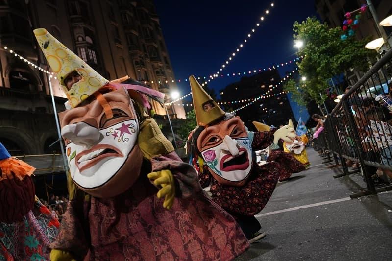 Dos cabezudos con la cara pintada y narices largas desfilan por 18 de julio; sobre la avenida hay guirnaldas de luces de colores.