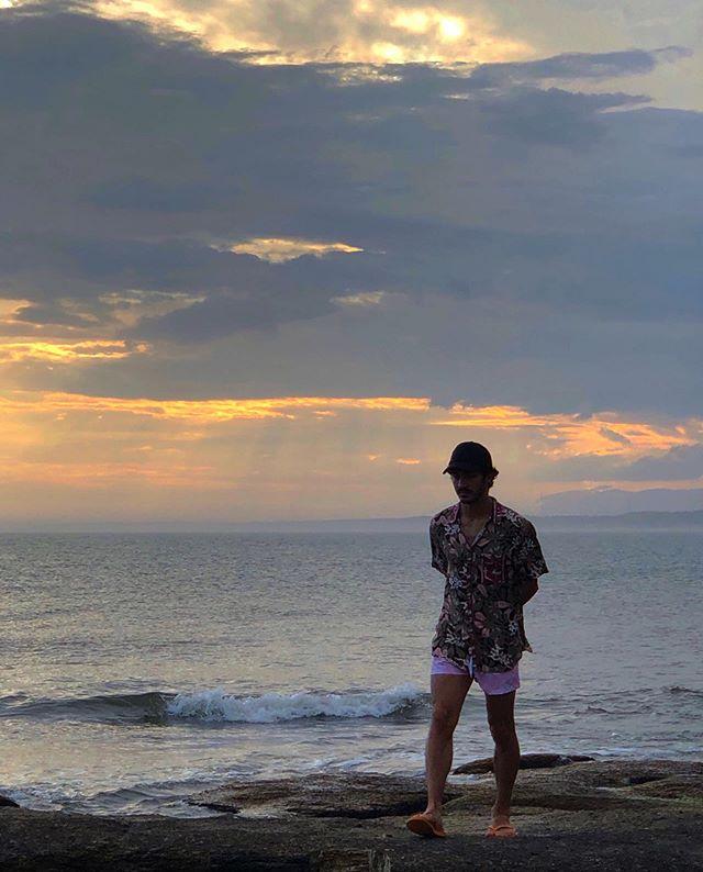 Chino Darín camina por la Playa de José Ignacio al atardecer en un día nublado.