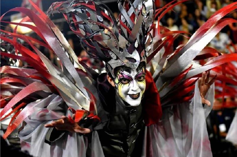 Un hombre con la cara pintada sonríe a la cámara; está vestido con un disfraz y un sonmbrero de formas irregulares de colores rojo, blanco y negro