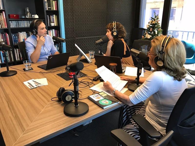 Andrés Gil, Romina Andrioli y Rosario Castellanos en torno a una mesa cuadrada dentro de un estudio de radio en el que hay una biblioteca y un pequeño árbol de navidad