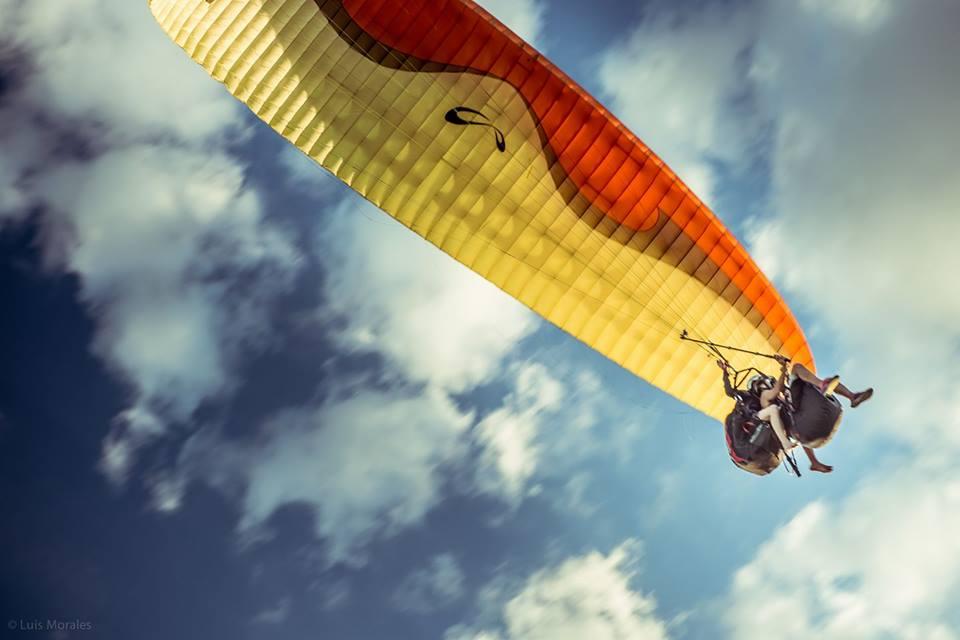 Imagen de dos personas volando en un parapente amarillo y naranja, vistos desde abajo; sobre el parapente se observa un cielo celeste con algunas nubes blancas