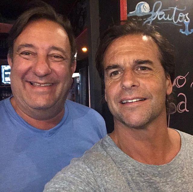 Imagen en primer plano de Luis Lacalle Pou junto al periodista Sergio Herrera, sonrientes, de frente a la cámara, dentro de un restaurante