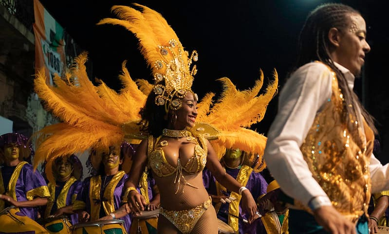 Imagen de una vedette bailando al frente de varias personas que tocan tambores