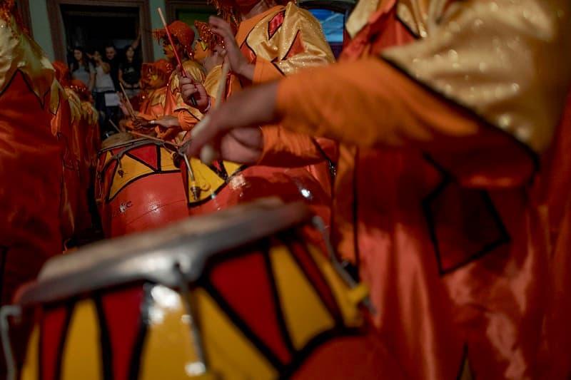 Varias personas tocan tambores pintados de rojo y amarillo en un desfile de llamadas